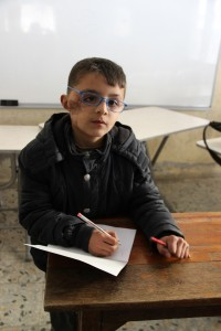 "Turkey, March 2014. 9 year old Safi like spelling the most. H was hurt by shrapnel fragments during bombing in Syria and he now lives in Antakya in Turkey. ""I'm from Latakia. I'm nine years old. I'm a second grade student. My favorite subject at school is spelling. I want to be a doctor when I grow up. When I wake up in the morning, I wash my hands and face first, and then I brush my hair. I go to school at 8 o'clock and I do my homework in the afternoon. Later, I play games in the big park and in the evening I have dinner. I like football — I'm a fan of FC Barcelona. I have two sisters and a brother, but I'm the eldest. My school in Syria closed because of the war. An airplane dropped a barrel bomb on our school. The poorest people ran away after the bomb, which shattered all the windows in our house. I was hurt when they dropped another bomb. I got shrapnel fragments in my face and back. Someone from our village was going to take me to the hospital, but we couldn't go because it was too far away from Latakia and it would take a lot of time. I still have some shrapnel in my back, but I wasn't afraid at those moments at all. I didn't feel anything. I'm not afraid of airplanes. I am afraid of bears, dogs and wild animals. Syria is more beautiful than here. I miss our house the most. I miss everything there.I want to save people from oppression. I want to become a doctor and I want to help people who are affected by the war and to save their lives. My third wish is to help thieves to persuade them not to steal. I have a friend. I love him so much, but I can't remember his name. Some of my friends are frightened of me because of the scar on my face. They don't want to play with me."" According to his teacher, he will have another operation in 20 days with the help of Kuwaiti benefactors."