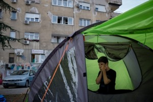 "On 6 October 2015 in Serbia, Munir Yousufi, 16, an unaccompanied minor traveling alone from Afghanistan, prays in a tent in a park by the bus station in downtown Belgrade. Serbia is a transit country for many refugees and migrants on the move in Europe, and the park by the central bus station has become a resting spot for those with tents. Munir grew up in Kunduz, and his family left that city when the Taliban destroyed their house, with them in it, during fighting. In the attack, Muneer lost partial use of the left side of his body, including his eye, arm and leg. ""We escaped to Mazar-a-Sherif, because the situation in Kunduz was too dangerous. But all of Afghanistan is too dangerous, so my family collected all of their money and sent me here for security, and to get new citizenship."" He said. Munir was traveling with other people from Mazar, but ten days ago, he ran out of money, and has been stuck in Belgrade since, living out of a tent in the park. His traveling companions continued to Germany, and ""I am relying on other Afghans to give me a little bit of money until I can get enough to get to Germany."" In September 2015, growing numbers of refugees and migrants seeking safety in Europe continue to enter or pass through Serbia. Many of them are fleeing violence, conflict and insecurity in their countries of origin. By 25 September, 141,259 people had expressed their intent to seek asylum in the country. They are among the 487,497 refugees and migrants who have arrived in Europe by sea in 2015. About one in every four asylum seekers in Europe so far this year has been a child. More than 130,000 children sought asylum between January and July – an average of over 18,000 children every month. A significant number of children are travelling unaccompanied or have become separated from their families on the move. As if their current plight were not distressing enough, the vast majority of children seeking refuge in Europe are escaping horrors we can only"