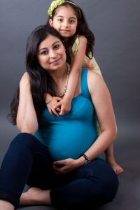 24666669 - portrait of a smiling, pregnant east indian woman sitting with her daughter