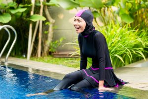 33765804 - muslim woman or girl sitting at pool in tropical garden wearing burkini halal swimwear