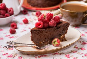 44351306 - homemade chocolate cake with raspberry on plate, cup of coffee and barries on side, selective focus