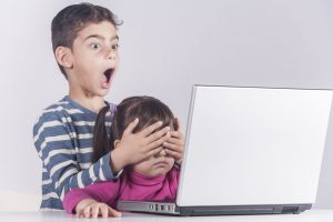 55052813 - little boy protects his sister from watching inappropriate content while using a computer. internet safety for kids concept. toned image with selective focus