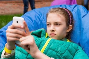 57717445 - young girl relaxing checking out her mobile phone for messages with a serious expression